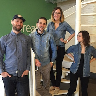 4 employees dressed the same: jeans shirt and black pants
